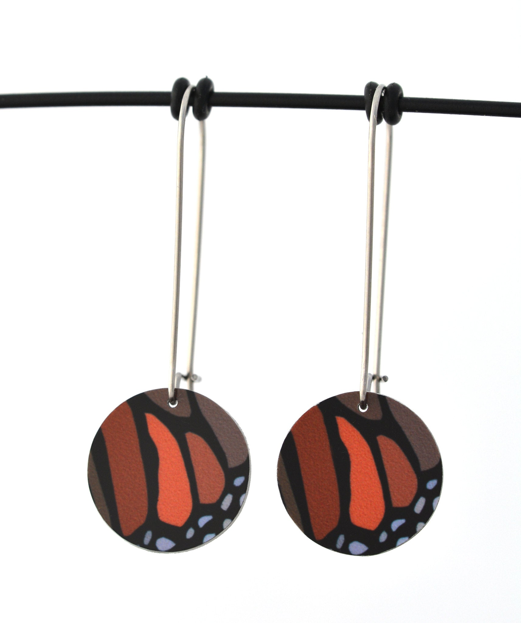 Circular earrings featuring the colours and shapes of a monarch butterfly wing. The aluminium earring discs are approximately 16mm in diameter and the surgical stainless steel drop hooks are 33mm long.