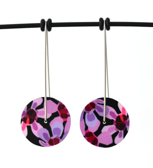 Circle earrings featuring pink Geraldton Wax flowers on a black background. The aluminium earrings discs are approximately 26mm in diameter and the surgical stainless steel drop hooks are approximately 40mm in length.