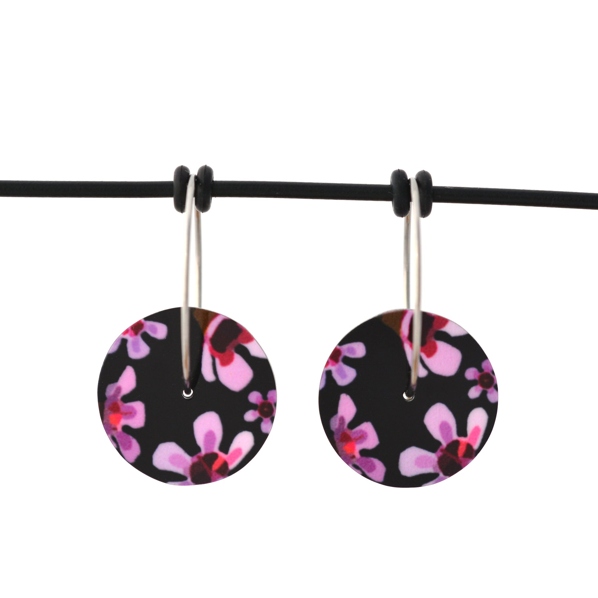 Circle earrings featuring pink Geraldton Wax flowers on a black background. The aluminium earrings discs are approximately 16mm in diameter and the surgical stainless steel hoop attachments are 20mm in diameter.