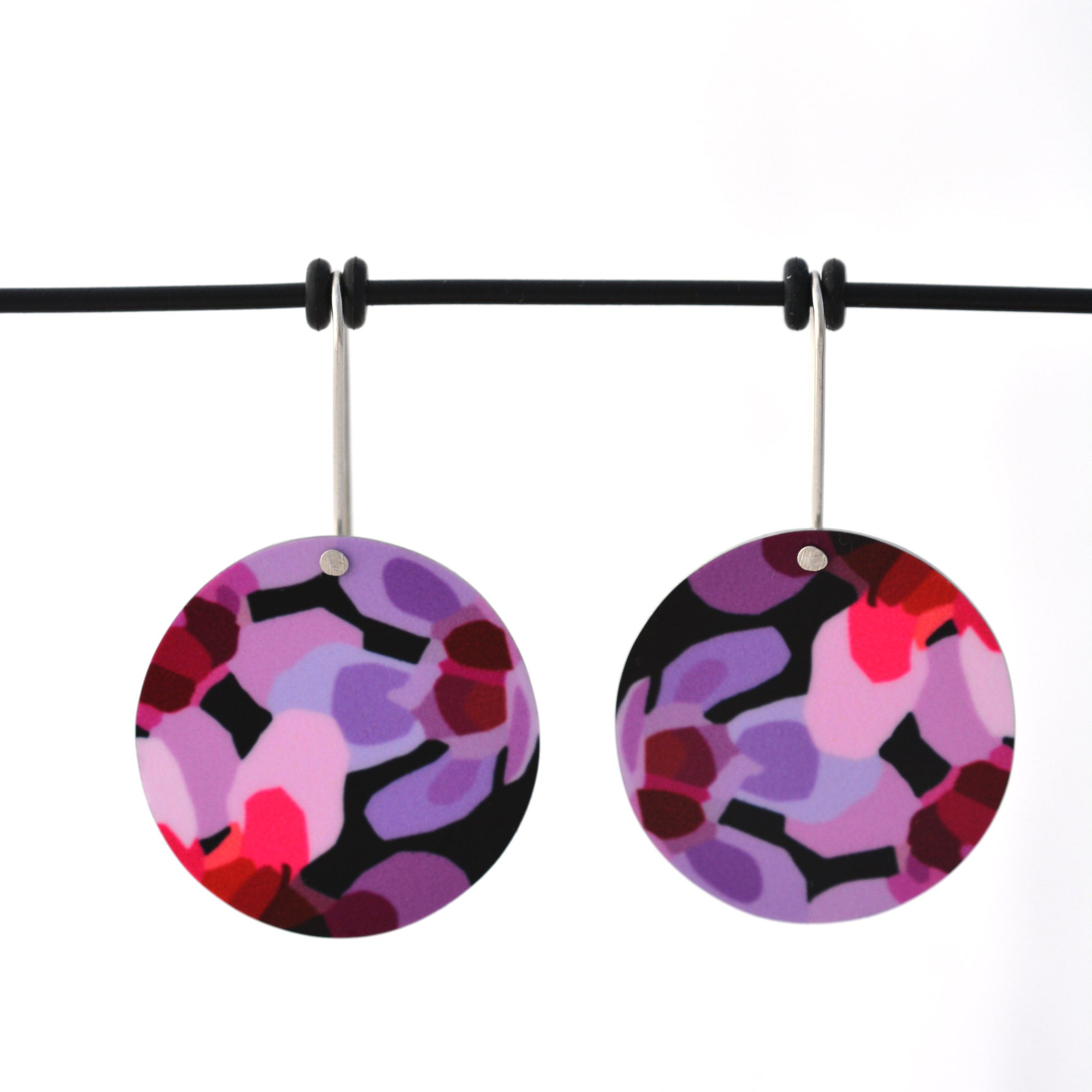Circle earrings featuring pink Geraldton Wax flowers on a black background. The aluminium earrings discs are approximately 26mm in diameter and the surgical stainless steel shepherds hooks are 15mm in length.