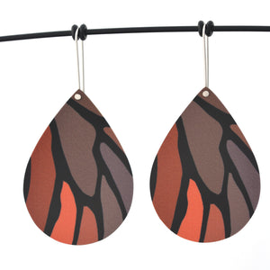 Droplet earrings featuring details from a monarch butterfly wing. The aluminium earrings are approximately 40mm long and 29mm wide. The 15mm long shepherds hooks are surgical stainless steel.