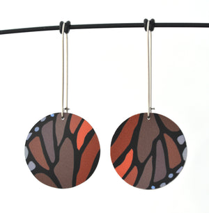 Circular earrings featuring the colours and shapes of a monarch butterfly wing. The aluminium earring discs are approximately 26mm in diameter and the surgical stainless steel drop hooks are 33mm long.