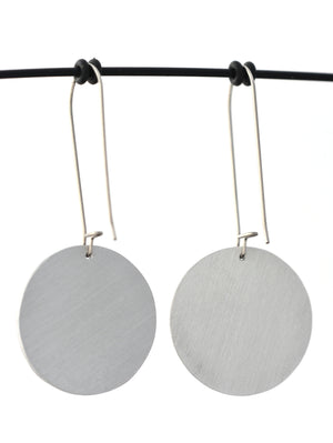 Brushed aluminium backs of circular earrings featuring the colours and shapes of a monarch butterfly wing. The aluminium earring discs are approximately 26mm in diameter and the surgical stainless steel drop hooks are 33mm long.