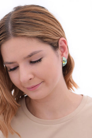 This image shows a woman wearing a Kitty Came Home stud earring in her left ear. The semi circle shape is 25 millimetres in diameter. The design is daylight drive by Satin and Tat. Green and yellow shapes form a landscape of gently rolling hills beneath a pale green sky.