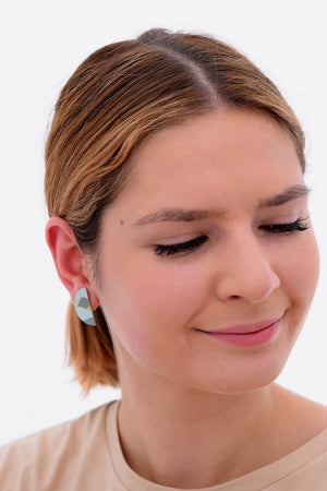 This image shows a woman wearing a Kitty Came Home stud earring in her right ear. The semi circle shape is 25 millimetres in diameter. The design is daylight drive by Satin and Tat. Green and yellow shapes form a landscape of gently rolling hills beneath a pale green sky.