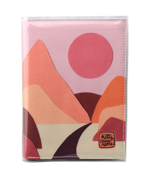 This is an image of the front of a Kitty Came Home A5 journal in the 'Lilly of the valley' design by Satin and Tat. A pink sun in a dusty pink sky above a landscape of orange, pink, burgundy and magenta hills. A path leads between the hills toward the distant mountains.