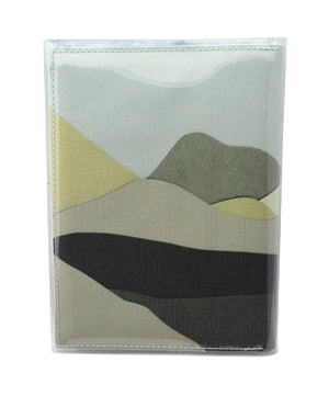 This is an image of the rear of a Kitty Came Home A5 journal in the 'Moonlight drive' design by Satin and Tat. A landscape of green hued hills beneath a pale green sky.
