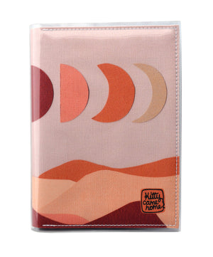 This is an image of the front of a Kitty Came Home A5 journal in the 'Moonshadow drive' design by Satin and Tat. The moon appears in all its phases in a dusty pink sky above a landscape lit by the moon's colours: burgundy, oranges, and apricot.