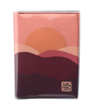 This is an image of the front of a Kitty Came Home A5 journal in 'The night comes down' design by Satin and Tat. An orange sun in a pink sky sinks behind a pink and magenta landscape of rolling hills.