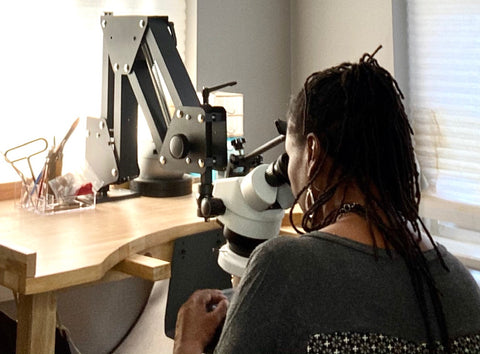 Candace Stribling at microscope setting stones in jewelry