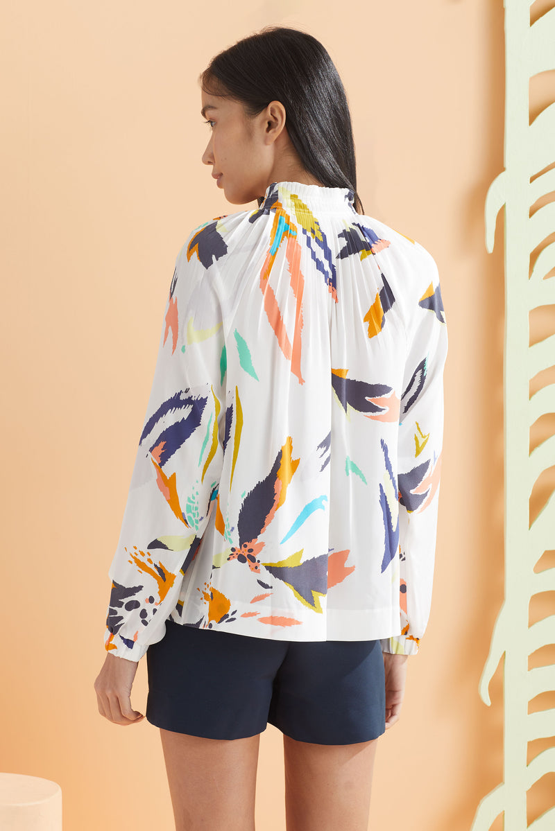 Long sleeve white and floral blouse worn with navy shorts, back