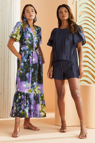 model wearing long tie dye maxi dress in green and purple with another model in navy short sleeve textured top and coordinating shorts.