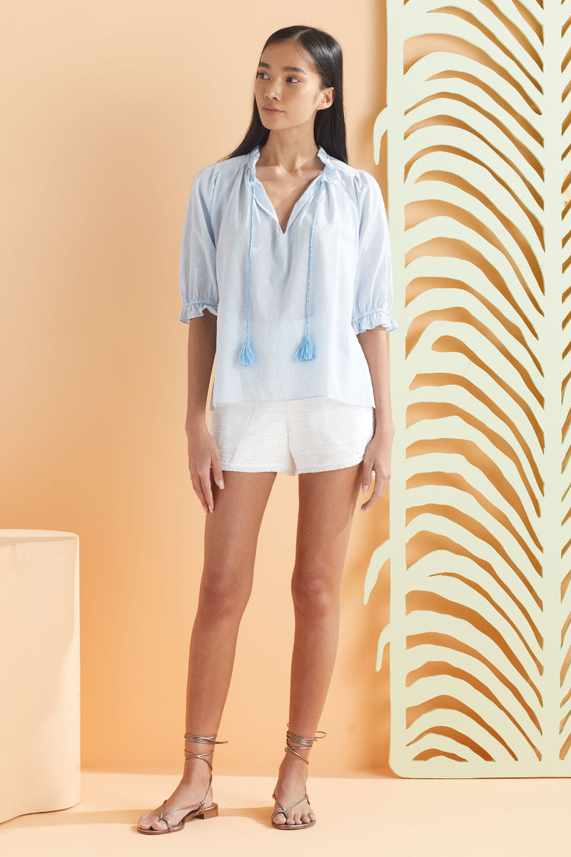 model wearing light blue and white stripe top