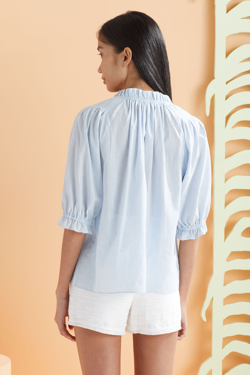 blue and white thin stripe top worn with white shorts, back