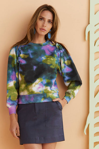 Model wearing navy skirt with tie dye sweatshirt