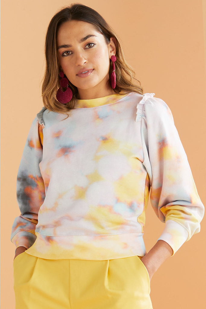 Model wearing pastel tie dye sweatshirt with yellow shorts.