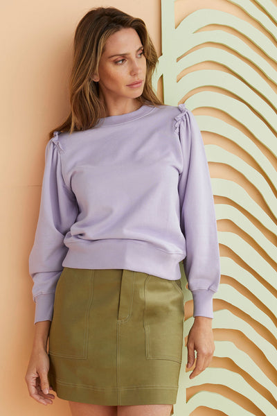 Lilac cotton Sweatshirt worn with green skirt.