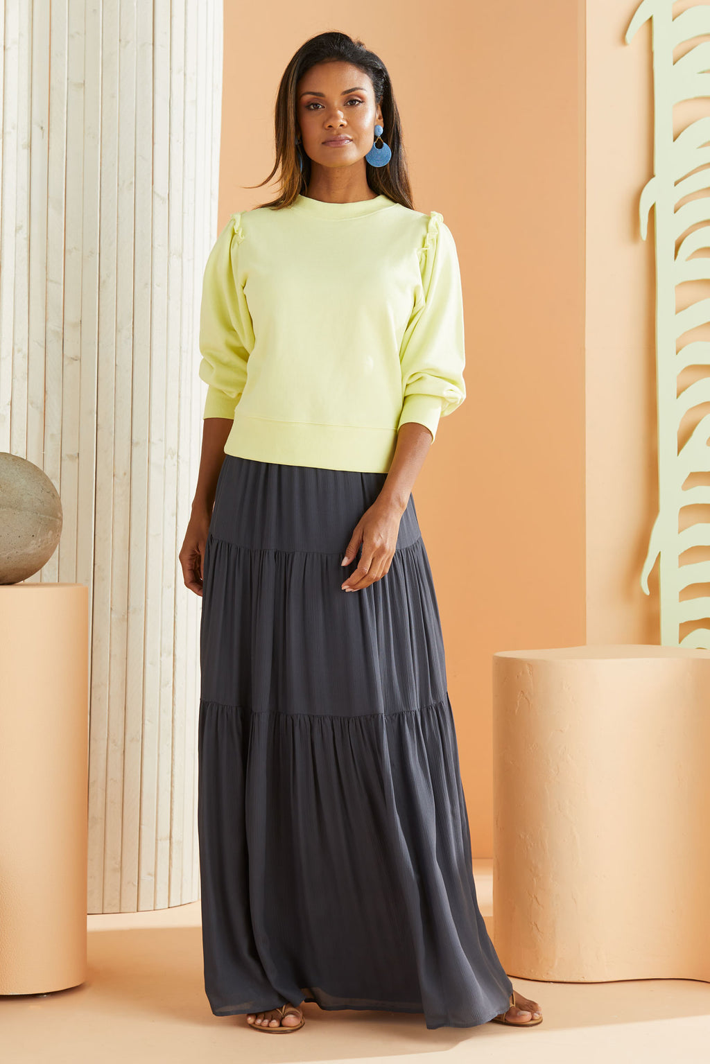 Lime sweatshirt worn over navy maxi dress.