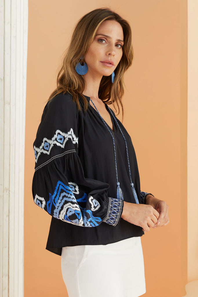 model wearing dark navy blouse with ikat embroidery