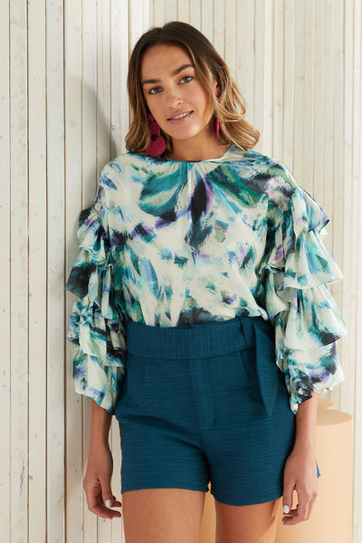 ruffle sleeve blouse worn with green sash shorts