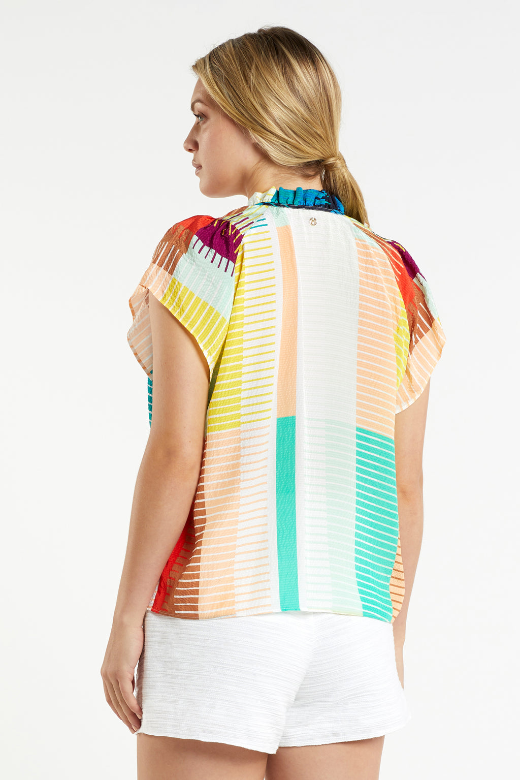 Model wearing short sleeve raglan blouse in multi colored geometric print with white shorts, back view.