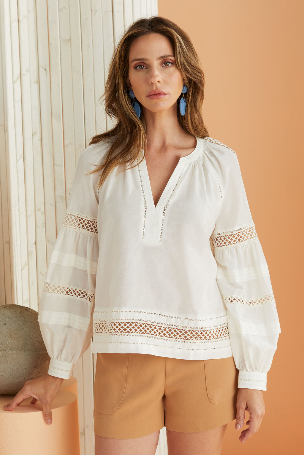 model wearing long sleeve white blouse with nude shorts.