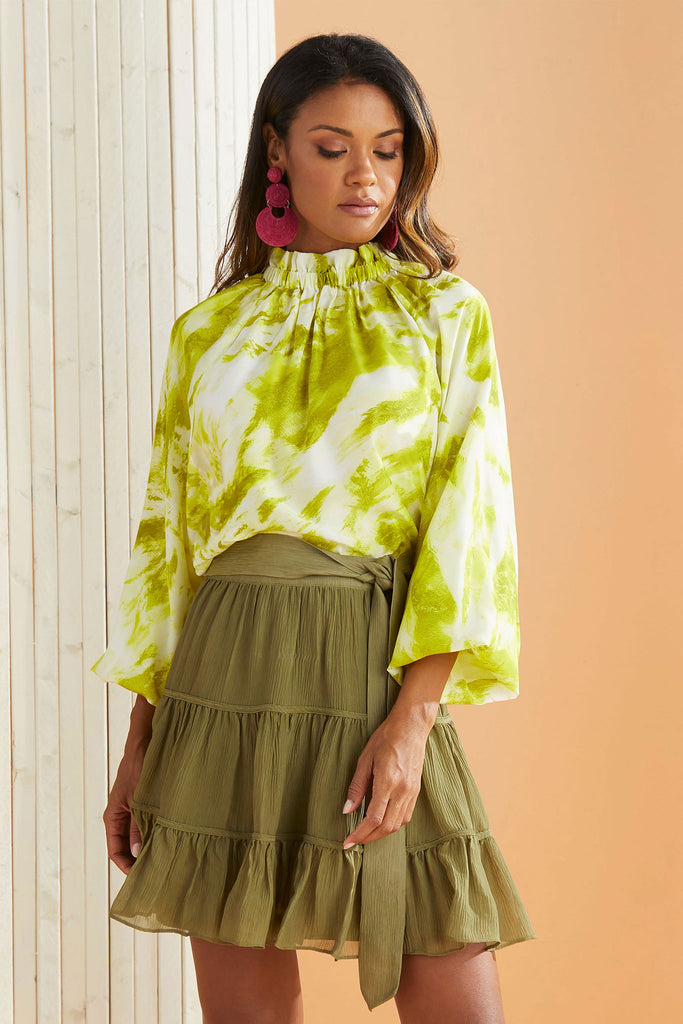 Model wearing the June Blouse in Citrus Tie Dye with the Bess Skirt in Olive
