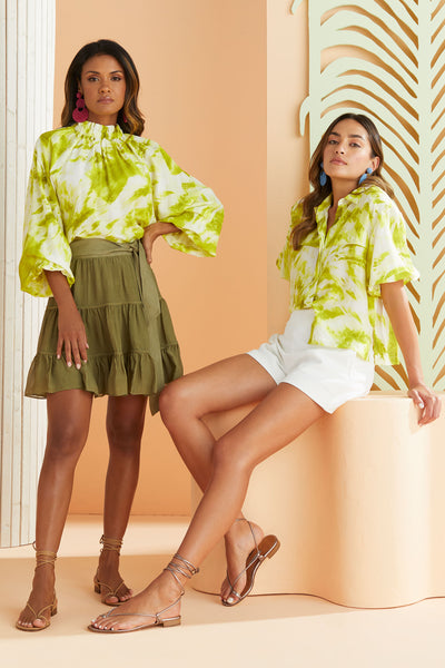 two models wearing matching lime green and white tie dye tops and olive short skirts