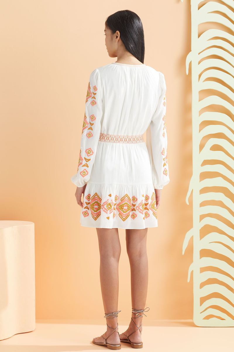 Model wearing long sleeve dress that hits above the knee in white and summer ikat, back view.