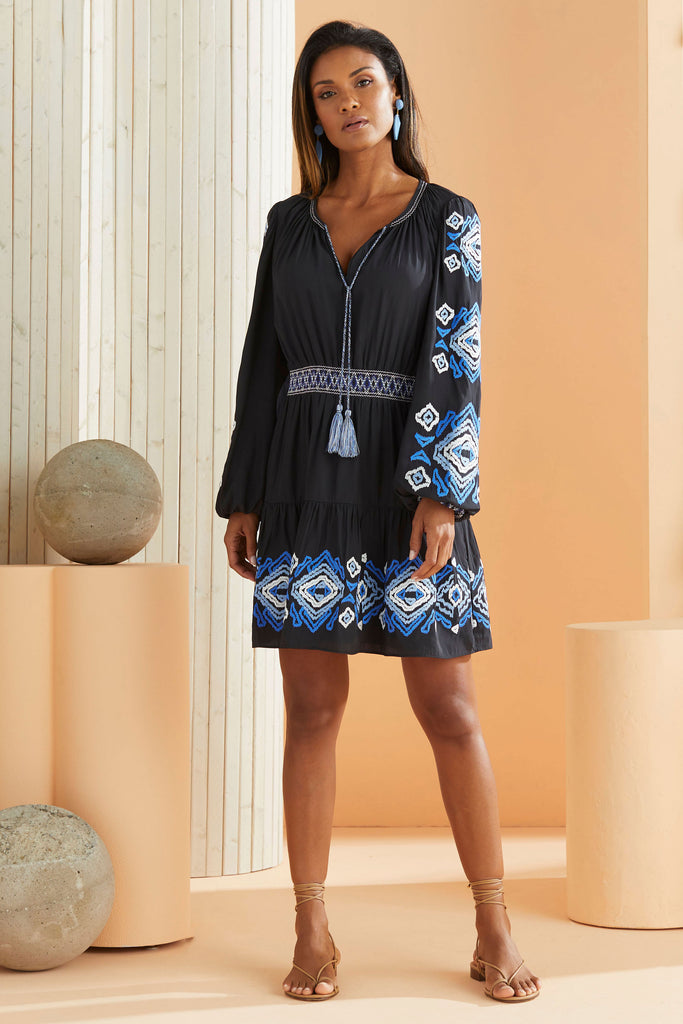 model wearing short dress with long sleeves that has ikat embroidery details