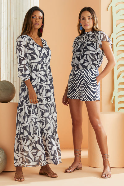 model wearing navy tropical leaf printed maxi dress standing next to another model in navy tropical leaf printed short sleeve blouse and shorts in zebra print
