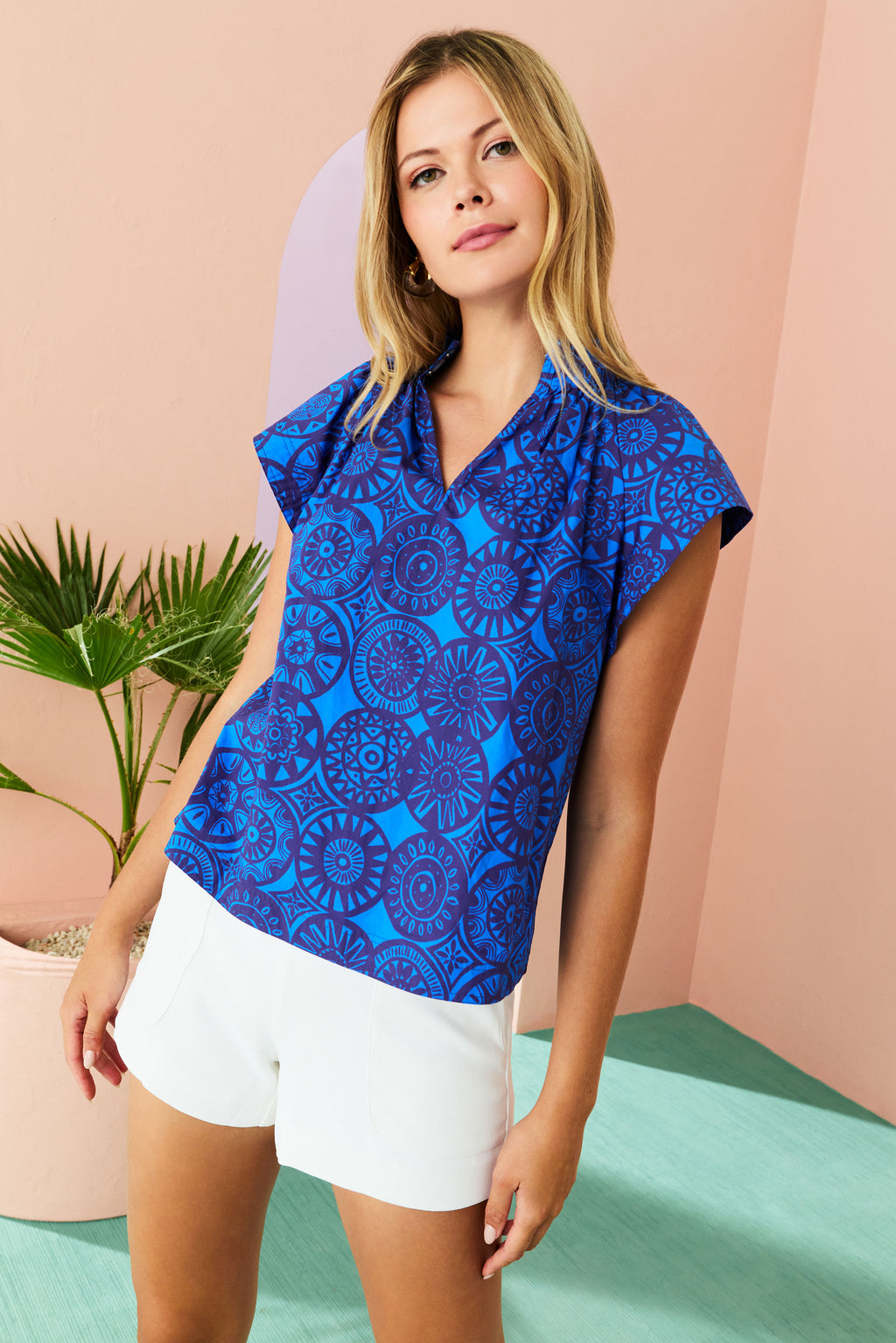 model in ombre colored top of orange, pink and blue with white tailored shorts