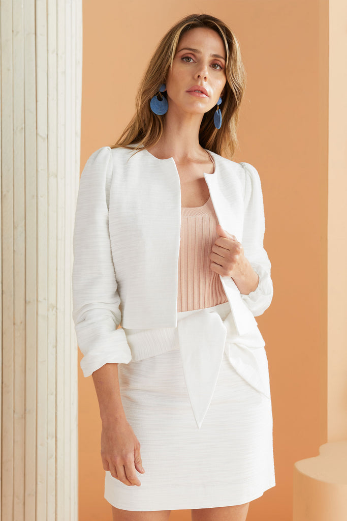 model wearing white textured jacket and skirt with tie waist