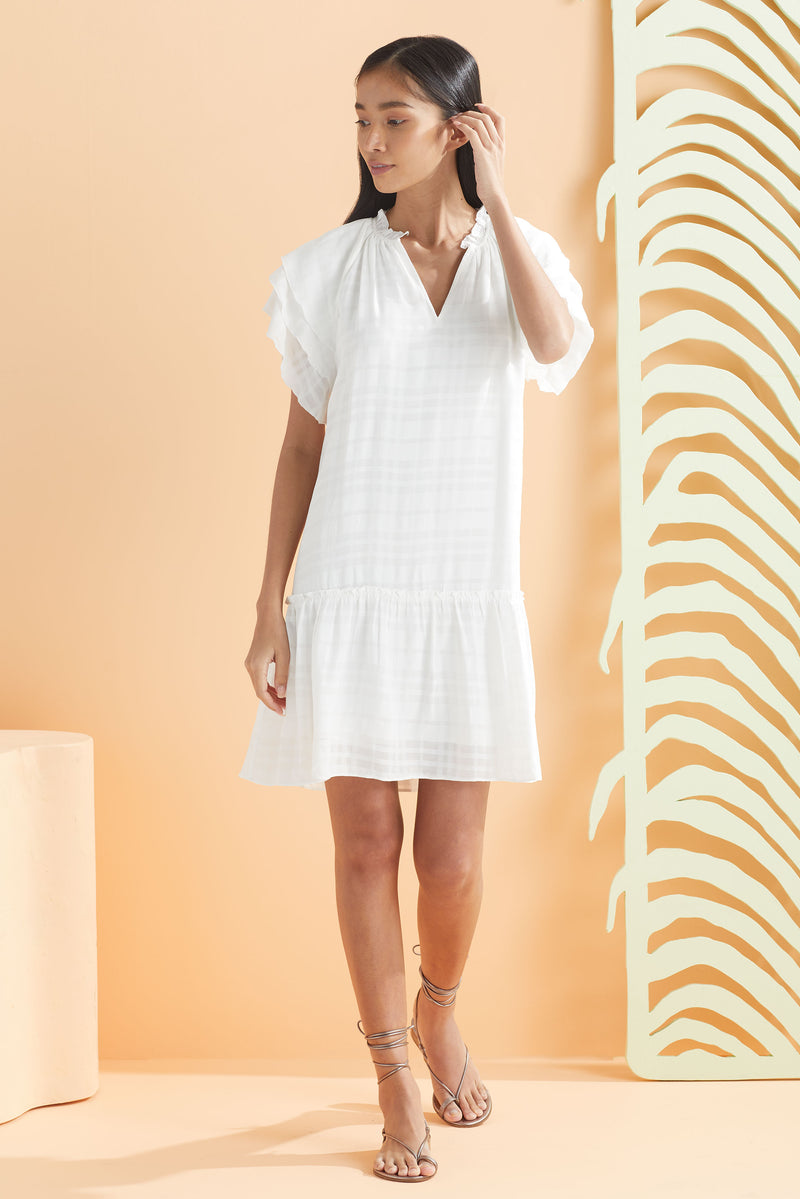 model wearing white plaid short dress with raglan sleeve detail and ruffle flounce hem