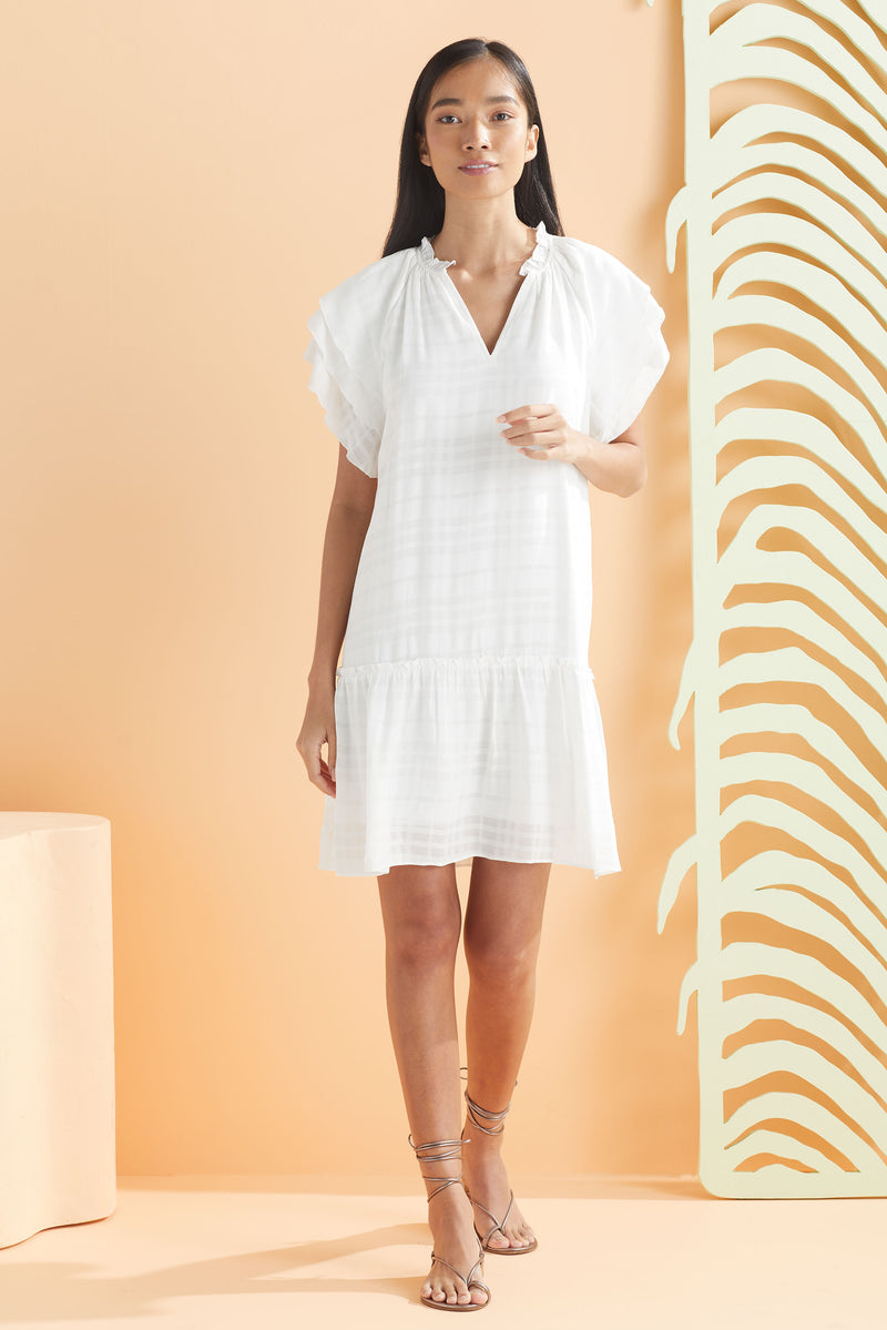 model wearing white plaid textured short dress with raglan sleeve detail and ruffle flounce hem