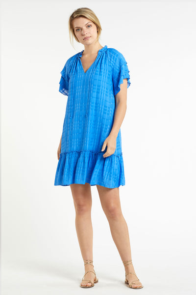 model wearing bright ocean blue tonal plaid short dress with raglan sleeve detail and ruffle flounce hem