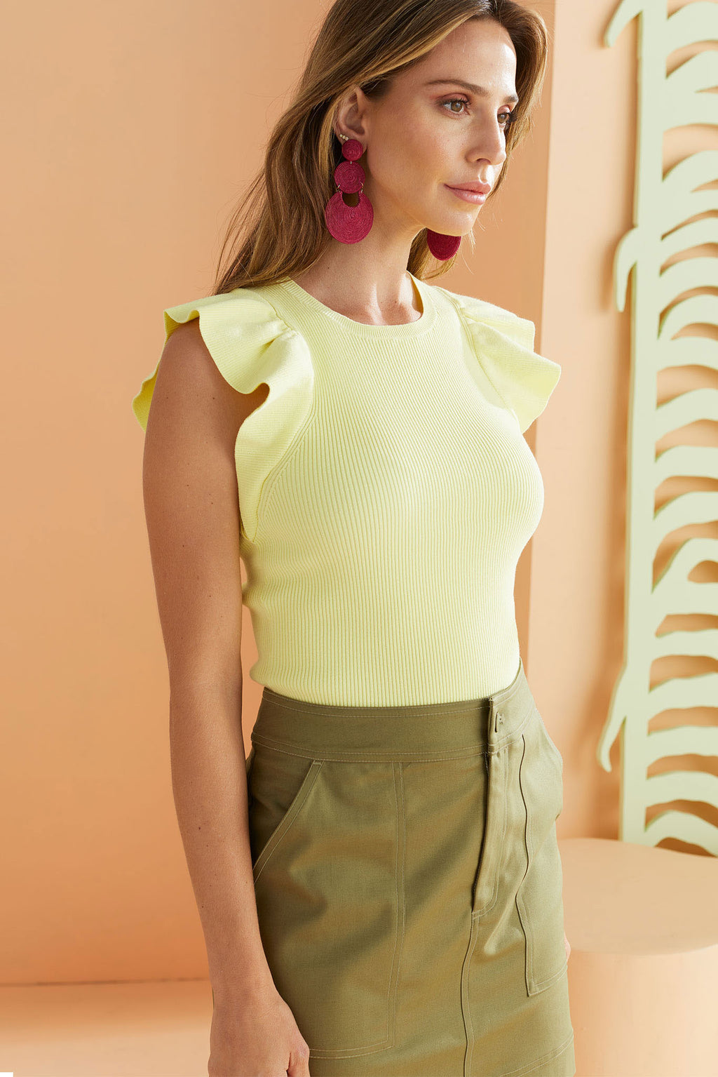 lemon lime citrus colored knit top with ruffles on shoulders. worn with olive green pencil skirt.
