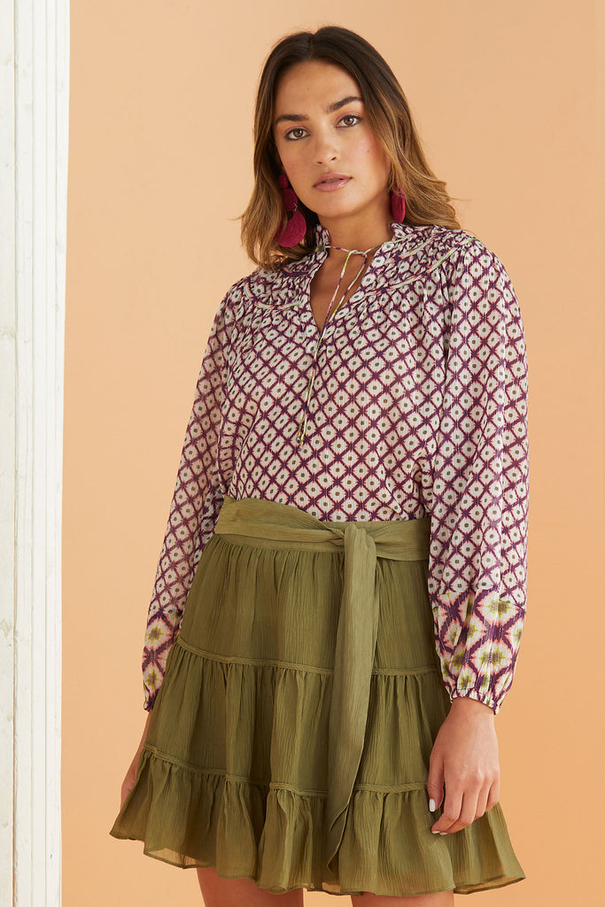Model wearing the Stori Blouse in Berry Lattice with the Bess Skirt in Olive.