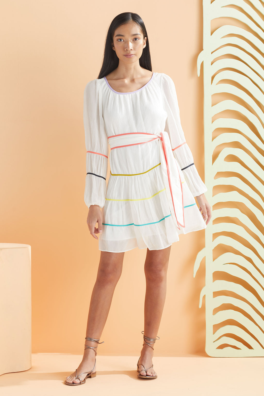 white longsleeve dress with multicolor piping details along tiers