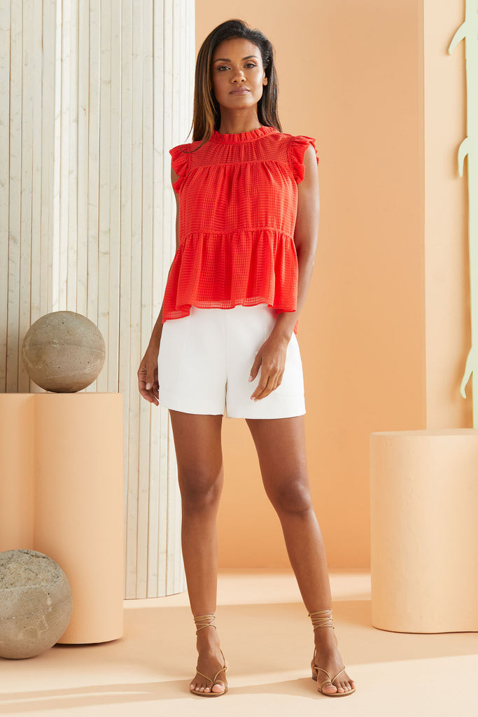 Model wearing the Tia Top in Cayenne red with Mia white shorts.