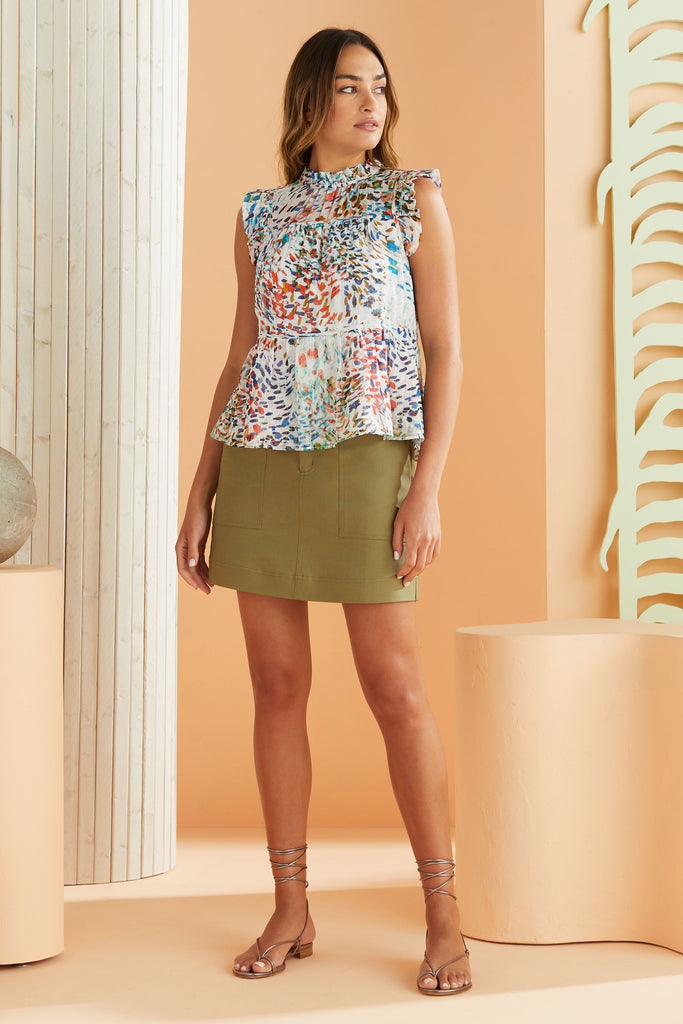 colorful cheetah print top worn with solid green skirt.