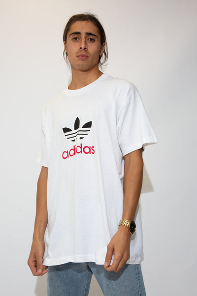 model is wearing a white adidas tee that features the words adidas in red