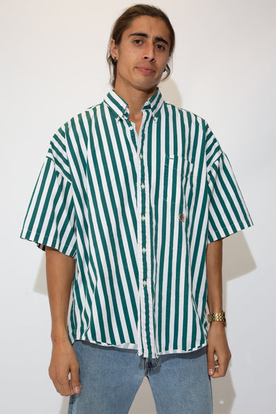 Model is wearing a green and white striped short sleeve button up made by tommy hilfiger