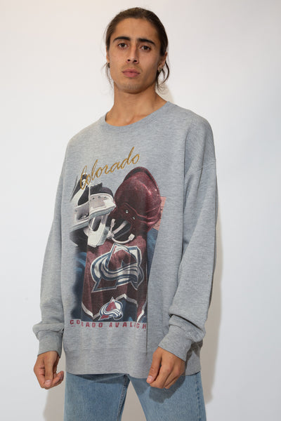 The model is wearing a grey sweater that features an embroidered Colorado on top of sports equipment