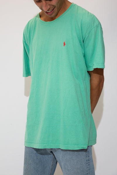 The model is wearing a greenish blue ralph lauren tee that fits boxy