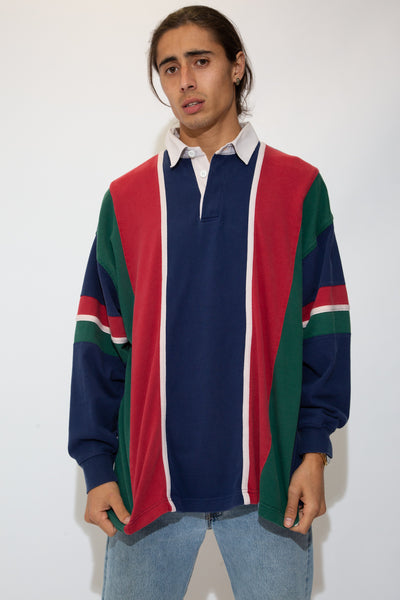 model is wearing a green blue red and white striped rugby that features a thick white collar
