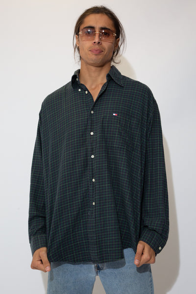 Model is wearing a green flannel button up made by tommy hilfiger the button up fits oversized on the model.