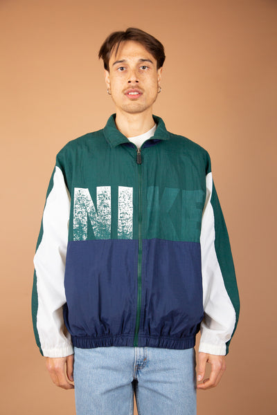 "Green, Navy and white jacket with Faded ""Nike"" on the front and large Nike logo on the back. 90's vintage at magichollow"