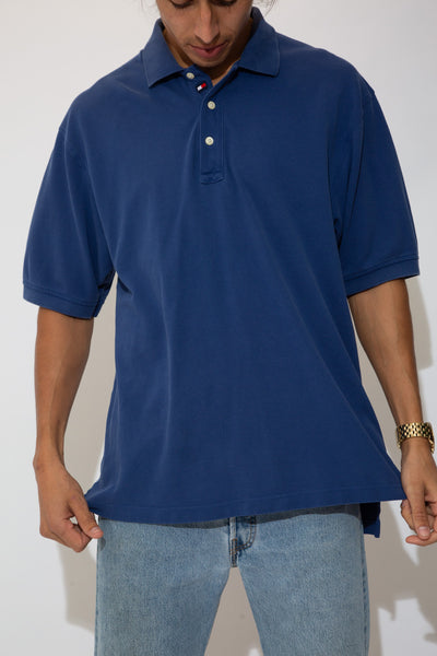 The model is wearing a blue Tommy Hilfiger polo that features a hidden tommy flag near the top buttons and a flag on the left sleeve near the cuff