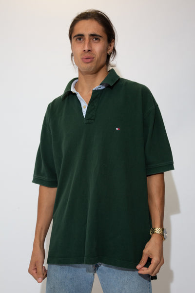 The model is wearing a green polo that features the Tommy flag on the left chest.